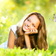 Spring Beauty. Beautiful Girl Lying on Green Grass outdoor — Stock Photo #21975035