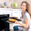 Happy Young Woman Cooking Pizza at Home - Stock Photo