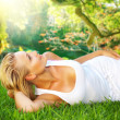 Beautiful healthy Young Woman relaxing on the green grass  — Stock Photo