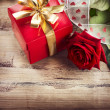 Valentine. Rose Flower and Gift Box over Wooden Background  — Stock fotografie