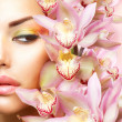 Beautiful Girl With Orchid Flowers. Beauty Model Woman Face - Foto de Stock  