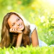 Spring Beauty. Beautiful Girl Lying on Green Grass outdoor — Stock Photo #21975795
