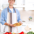 Young Man Cooking Pizza - Stock Photo