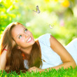 Spring Beauty. Beautiful Girl Lying on Green Grass outdoor - Stok fotoğraf
