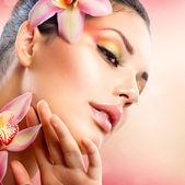 Krásné lázeňské dívka s květy orchidejí dotýká její obličej — Stock fotografie