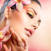Vackra spa flicka med orkidé blommor röra hennes ansikte — Stockfoto