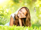 Belleza de primavera. hermosa chica tumbado en la hierba verde al aire libre — Foto de Stock
