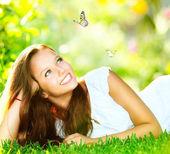 春の美しさ。屋外の緑の草の上に横たわる美しい少女 — ストック写真