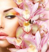 Piękna dziewczyna z kwiaty orchidei. twarz uroda wzór kobiety — Zdjęcie stockowe