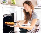 Gelukkig jonge vrouw pizza thuis koken — Stockfoto