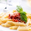 Pasta Penne with Bolognese Sauce, Basil and Parmesan — Stock Photo #24593339