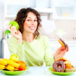 Dieting concept. Young Woman choosing between Fruits and Sweets - Stok fotoğraf