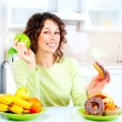 Stock Photo: Dieting concept. Young Woman choosing between Fruits and Sweets