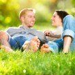 Park. Young Couple Lying on Grass Outdoor — Stock Photo #24593787