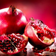 Stock Photo: Pomegranates over Red Background. Organic Bio fruits