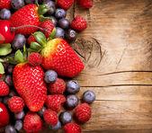 ягоды на деревянных фоне. органические берри над лесом — Стоковое фото
