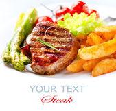 Gegrilltes rindfleisch steak mit gebratenen kartoffeln, spargel, tomaten — Stockfoto