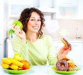 Concepto de dieta. mujer joven eligiendo entre frutas y dulces — Foto de Stock