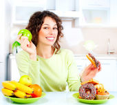 Dieting concept. Young Woman choosing between Fruits and Sweets — Стоковое фото