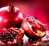Pomegranates over Red Background. Organic Bio fruits — Stock Photo