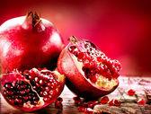Granátová jablka na červeném pozadí. organické bio ovoce — Stock fotografie