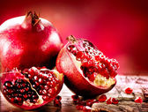 Pomegranates over Red Background. Organic Bio fruits — Zdjęcie stockowe