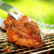 Foto de Stock  : Flames Grilling Steak on BBQ. Grill Beef Steak Barbeque