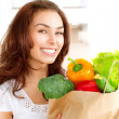 Happy Young Woman with vegetables in shopping bag — Stock Photo #29984237