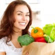Happy Young Woman with vegetables in shopping bag — Stock Photo