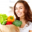 Stock Photo: Happy Young Woman with vegetables in shopping bag. Diet Concept