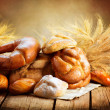 Stock Photo: Bakery Bread on Wooden Table. Various Bread and Sheaf
