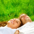 Happy Smiling Couple Relaxing on Green Grass. Park — Stock Photo #29985475