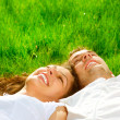 Stock Photo: Happy Smiling Couple Relaxing on Green Grass. Park
