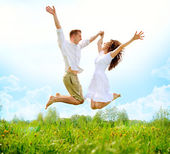 Happy Couple Outdoor. Jumping Family on Green Field — Stock Photo
