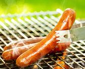 Salsichas grelhadas na grelha flamejante. para churrasco. bearbeque ao ar livre — Foto Stock