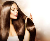 Krása ženy dotýkal její hnědé vlasy dlouhé a zdravé — Stock fotografie