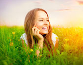 Beauty Girl in the Meadow lying on Green Grass with wild Flowers — Foto Stock