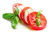 Caprese Salad. Tomato and Mozzarella slices with basil leaves — Stock Photo