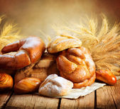Bakery Bread on a Wooden Table. Various Bread and Sheaf — Stock Photo
