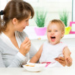 Mother Feeding Her Baby Girl with a Spoon — Stock Photo #35709567