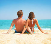 Young Couple Sitting together on the Beach. Vacation concept — Stock Photo