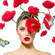 Stock Photo: Beauty Fashion Model Woman with Red Poppy Flowers in her Hair