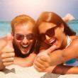 Happy Couple in Sunglasses having fun on the Beach — Zdjęcie stockowe #35710643