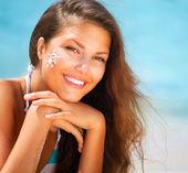 Beautiful happy Girl applying Sun Tan Cream on her Face — Stock Photo