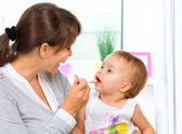 Mother Feeding Her Baby Girl with a Spoon — Stock Photo