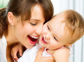 Happy Smiling Mother and Baby kissing and hugging at Home — Stock Photo