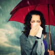 Stock Photo: Sneezing Womwith Umbrellover Autumn Rain Background