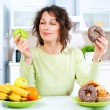 Dieting concept. Young Woman choosing between Fruits and Sweets — ストック写真