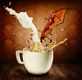 Coffee With Milk Splashing. Cup of Cappuccino or Latte — Stock Photo