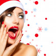 Stock Photo: Christmas Woman. Beauty Model Girl in Santa Hat over White